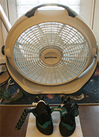 Shoes sitting in-front of a fan to dry.