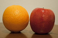 An orange and apple on the table.