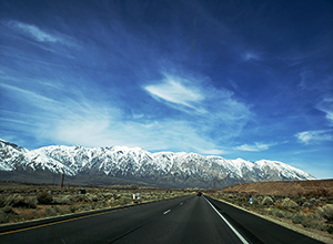 Driving on a highway from Bishop, CA with mountains in foreground.
